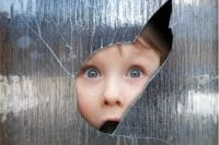 Young boy looking through a smashed window